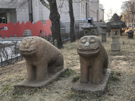 Stone lions with Cheshire Cat grins